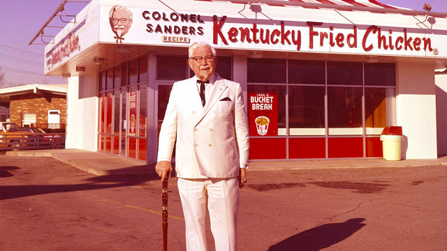 Ο Colonel Sanders μπροστά από το Kentaky Fried Chicken